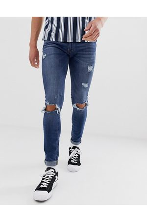 Jack & Jones Intelligence spray on skinny jeans with rip detail in mid blue