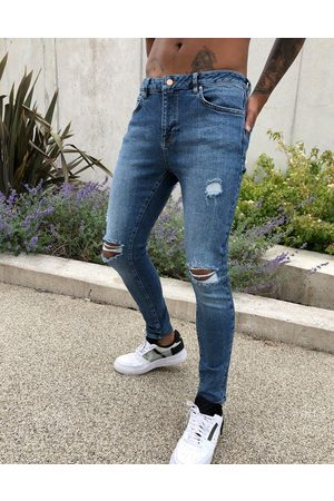 ASOS Spray on'vintage look' jeans with power stretch in dark wash blue with abrasions-Blues