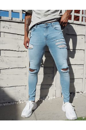 ASOS Spray on 'vintage look' jeans with power stretch in light wash with heavy rips