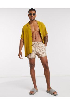 ASOS Swim shorts in stone seersucker with tonal palm print