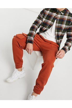 ASOS Tapered sweatpants with multi utility pockets & tab cuffs in burnt red