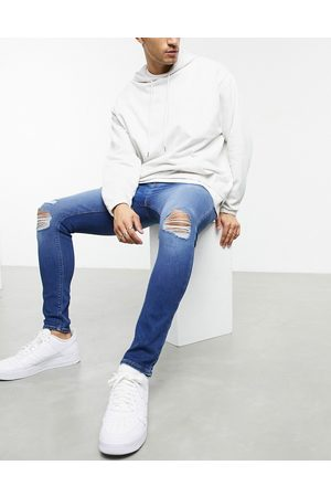 ASOS Spray on jeans in power stretch with 'less thirsty' wash in mid blue with knee rips-Blues