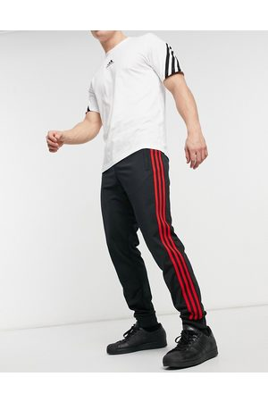 adidas 3-Stripes Firebird sweatpants in and red