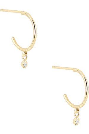 STONE AND STRAND Teeny Hanging Diamond Huggie Earrings in Metallic