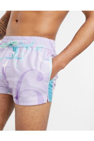 ASOS DESIGN Swim shorts in lilac with slogan super short length