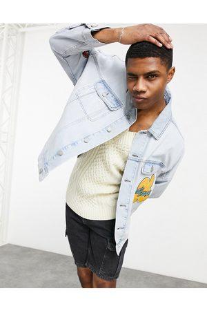 ASOS Oversized denim jacket with badging in lightwash blue-Blues