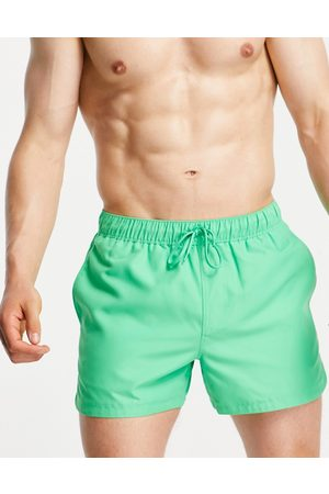 ASOS DESIGN Swim shorts in bright with curved hem in short length