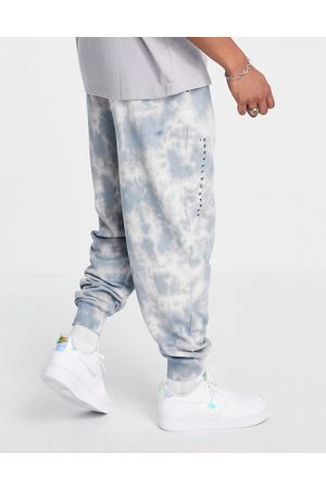ASOS Unrvlld Spply Relaxed sweatpants with all over wash & logo print in blue - part of a set-Blues