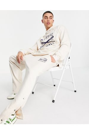 ASOS Coordinating relaxed straight leg sweatpants with vintage sports print and side snap detail in ecru