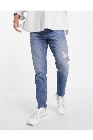 ASOS DESIGN Stretch tapered jeans in vintage dark wash with abrasions-Blues
