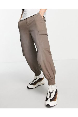 ASOS Oversized tapered pants with pigment spray in -Grey