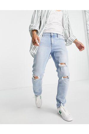 ASOS DESIGN Slim jeans with knee rips in vintage light wash blue-Blues