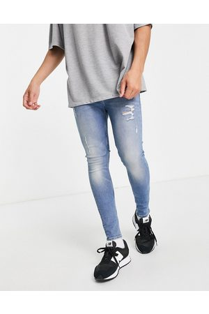 ASOS DESIGN Men Skinny - Organic cotton blend spray on jeans with powerstretch in vintage light wash with abrasions-Blues