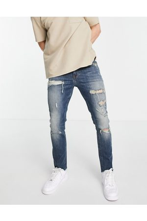 ASOS Skinny jeans with heavy rips and raw hem in tinted mid wash-Blues