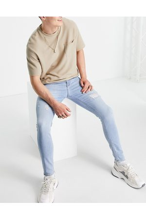 ASOS Spray on jeans with power stretch in 'less thirsty' light wash with rips-Blues