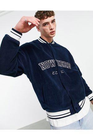 ASOS Oversized polar fleece varsity jacket in navy with chest applique